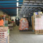 Inside of warehouse, stacks and bags of produce