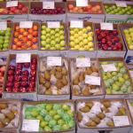 Boxes of fruit (red, yellow and green apples, pears, etc) on display.